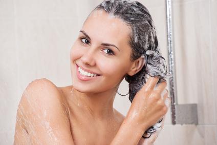 Frau wäscht sich die Haare mit Jojobaöl